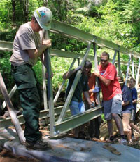Volunteers install a new bridge in Capitol State Forest.